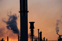 Smoking chimneys of a petroleum refinery at sunset by Sami Sarkis Photography