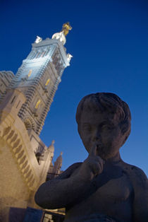 Stone statue of a cherub with view of the bell tower of Notre Dame de la Garde von Sami Sarkis Photography