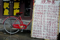 Red bicycle parked behind a long list of menu prices by a restaurant in Datong by Sami Sarkis Photography