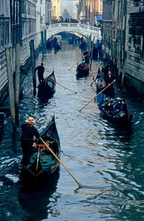 Tourists travelling on gondolas through a narrow canal by Sami Sarkis Photography