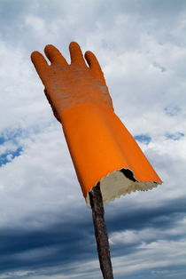 Orange rubber glove on a wooden post against a cloudy sky by Sami Sarkis Photography
