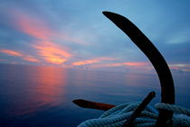 Rusty anchor with rope coiled around and view of the sunset over the sea in the background von Sami Sarkis Photography