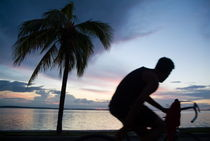 Man cycling along the waterfront at sunset by Sami Sarkis Photography