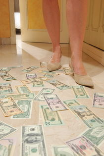 Woman's legs standing on money by Sami Sarkis Photography