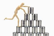 Wooden mannequin climbing tin cans pyramid von Sami Sarkis Photography