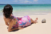 Woman in pareo lying on tropical beach by Sami Sarkis Photography