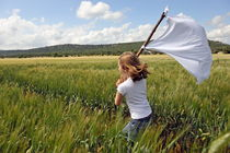 Girl with a white flag in wheat field von Sami Sarkis Photography