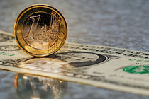 One Euro Coin standing up on US dollar banknote von Sami Sarkis Photography