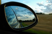 Close-up of side-view mirror reflecting clouds by Sami Sarkis Photography