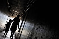 Mother and daughter walking in a dark corridor von Sami Sarkis Photography