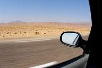 Side-view mirror of car speeding on desert highway von Sami Sarkis Photography