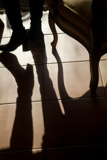 Shadow of woman's foot and furniture on floor by Sami Sarkis Photography