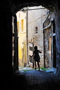 Girl running through a cobblestone street von Sami Sarkis Photography