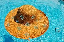 Straw hat floating on pool von Sami Sarkis Photography