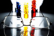 Spectacles and three colorful test tubes by Sami Sarkis Photography