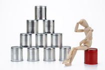 Mannequin on red can by a tin cans pyramid by Sami Sarkis Photography