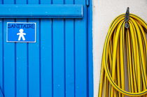 Men's closed bathroom door and hose by Sami Sarkis Photography