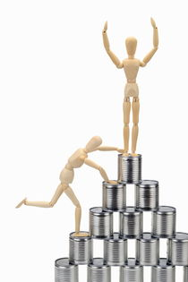 Wooden mannequin climbing tin cans pyramid by Sami Sarkis Photography