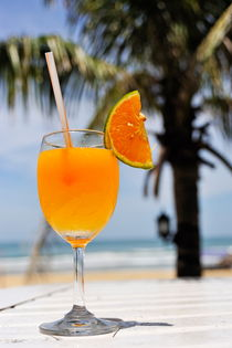 Glass of Orange cocktail by palm tree on beach by Sami Sarkis Photography
