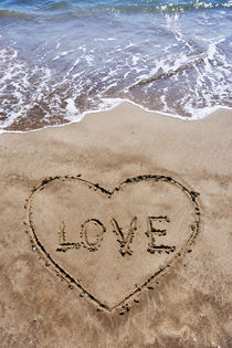 Heartshape drawn in sand on beach with Love word inside by Sami Sarkis Photography