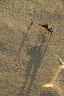Man leading two camels with tourists at sunset von Sami Sarkis Photography