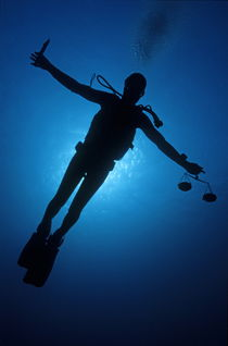 Silhouette of diver with knife and weight scale by Sami Sarkis Photography