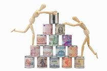 Two Wooden mannequins on worldwide banknotes pyramid von Sami Sarkis Photography