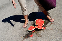 Woman standing by broken watermelon on asphalt by Sami Sarkis Photography
