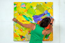 Woman adjusting a painting by Sami Sarkis Photography