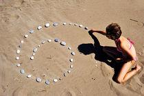 Girl on beach displaying pebbles in spiral shape von Sami Sarkis Photography