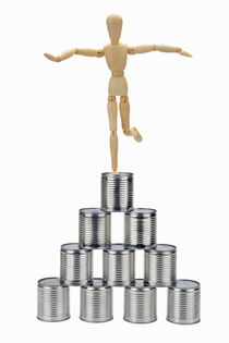 Wooden mannequin balancing on top of tin cans pyramid von Sami Sarkis Photography