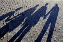 Family of four casting shadows on cobbled stone street von Sami Sarkis Photography