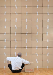 Businessman seated facing cardboard boxes wall by Sami Sarkis Photography