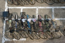 Bicycles parked in rows on a city street in Datong by Sami Sarkis Photography