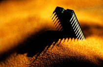 Computer chip half-buried in sand. by Sami Sarkis Photography