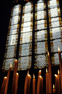 Candles burning in front of a stained glass window in the Auch Cathedral by Sami Sarkis Photography