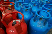 Rows of blue and red domestic gas bottles by Sami Sarkis Photography