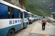Man searching among a row of tourist buses parked on Mount Hua von Sami Sarkis Photography