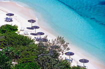 Sun umbrellas dotted along the white sand beach on Amedee Island by Sami Sarkis Photography