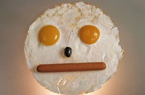 Fried breakfast of eggs and sausage made into a neutral face. von Sami Sarkis Photography