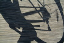 Shadow of a person riding a bicycle. by Sami Sarkis Photography