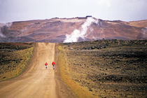 Two bikers on a dirt road leading to a geothermal power station at Myvatn by Sami Sarkis Photography