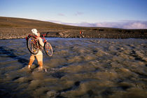 Man carrying bicycle on his shoulder crossing a river von Sami Sarkis Photography