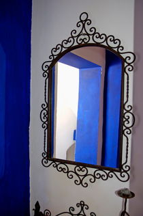 Ornate wrought iron mirror reflecting a window. by Sami Sarkis Photography