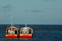 Two red fishing boats moored side by side in the blue ocean by Sami Sarkis Photography