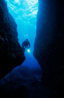 One scuba diver shines an underwater light while swimming through a cave von Sami Sarkis Photography