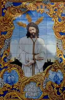 An azulejo ceramic tilework depicting Jesus Christ adorns a building exterior in the Compas de San Francisco by Sami Sarkis Photography