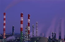 Petroleum refinery chimneys at dusk by Sami Sarkis Photography