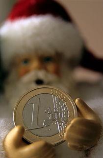 Santa Claus doll holding out a euro coin. von Sami Sarkis Photography