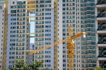 Construction crane in front of the facade of a large apartment building von Sami Sarkis Photography